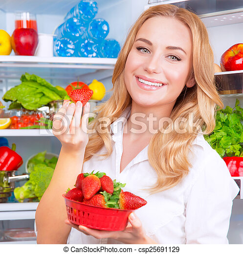 Beautiful woman eating strawberry - csp25691129