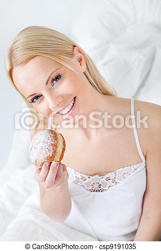 Beautiful woman eating tasty donut - csp9191035