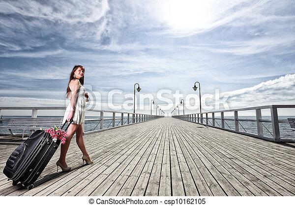 Beautiful woman girl sea mooring suitcase on a pier - csp10162105