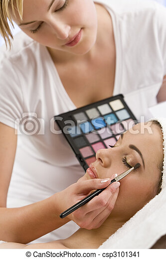 Beautiful Woman Having Make Up Applied by Beautician at Spa - csp3101341
