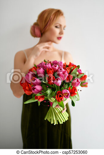 Beautiful woman hold bouquet of red and pink tulip flowers happy smiling on grey - csp57253060