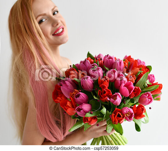 Beautiful woman hold bouquet of red and pink tulip flowers happy smiling on grey - csp57253059