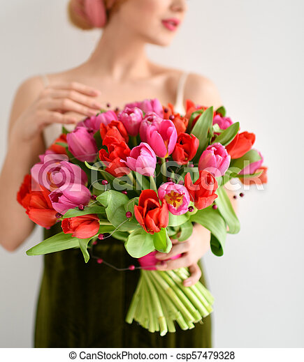Beautiful woman hold bouquet of red pink tulips flowers on grey - csp57479328