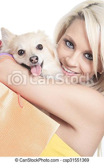 Beautiful woman holding dog in studio - csp31551369