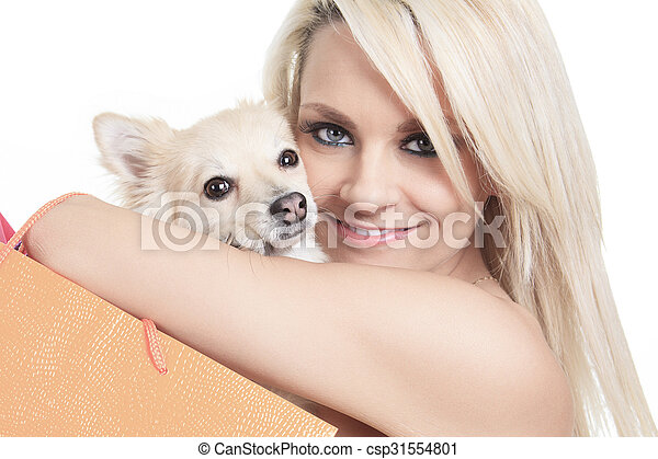 Beautiful woman holding dog in studio - csp31554801