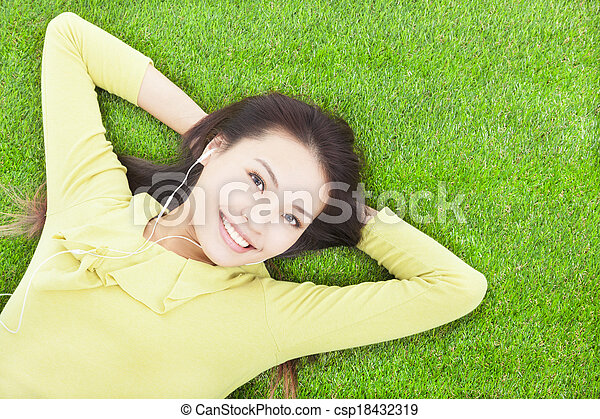 beautiful woman holding head and lying on a meadow - csp18432319