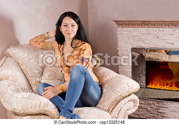 Beautiful woman in a comfortable armchair - csp13325148