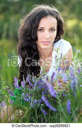 beautiful woman in a field with blooming flowers - csp26266621