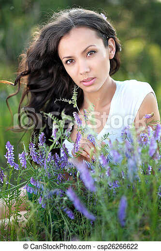 beautiful woman in a field with blooming flowers - csp26266622