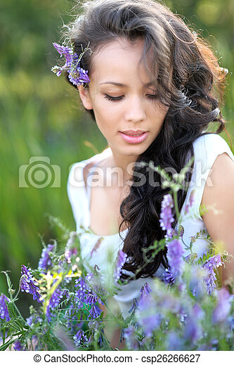 beautiful woman in a field with blooming flowers - csp26266627