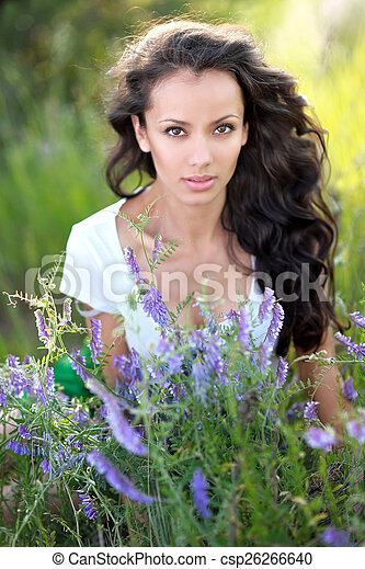 beautiful woman in a field with blooming flowers - csp26266640