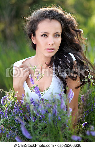 beautiful woman in a field with blooming flowers - csp26266638