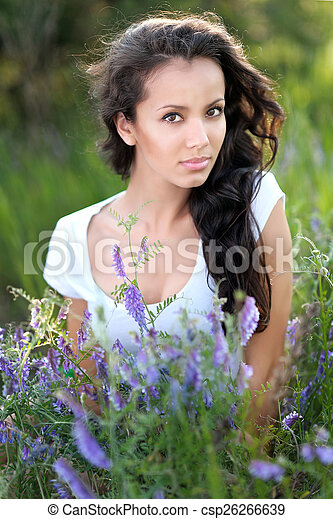 beautiful woman in a field with blooming flowers - csp26266639