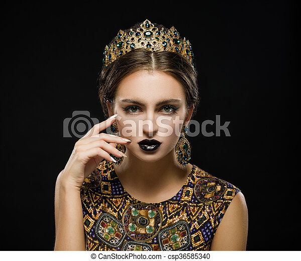 Beautiful woman in a golden crown and earrings on a dark background - csp36585340
