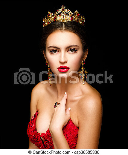 Beautiful woman in a golden crown and earrings on a dark background - csp36585336