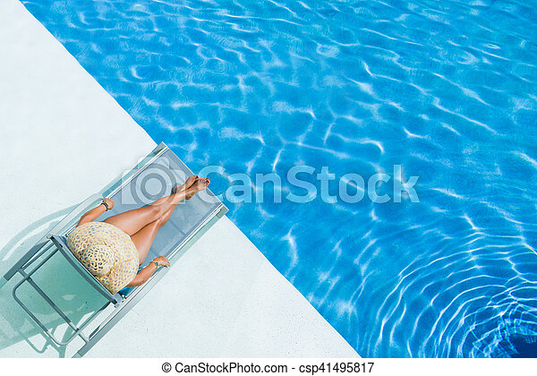 beautiful woman in a hat sitting on the edge of the pool - csp41495817