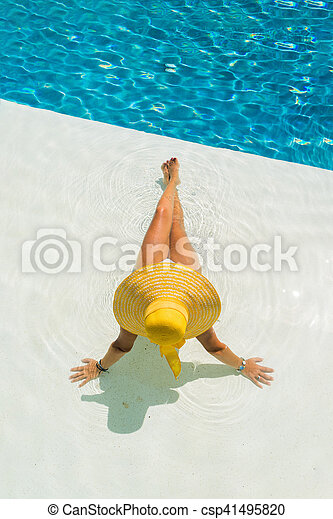 beautiful woman in a hat sitting on the edge of the pool - csp41495820