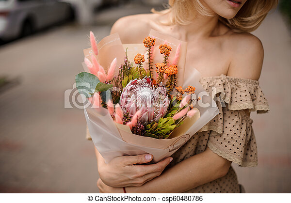 5cf52d0b89 Beautiful Woman In Beige Dress Holding A Nude Colored Bouquet Of Flowers  With Protea