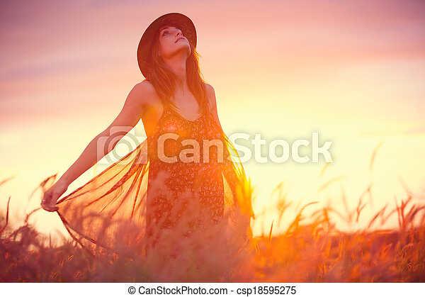 Beautiful woman in golden field at sunset - csp18595275