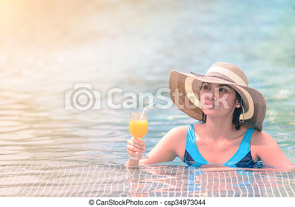 Beautiful woman in hat is holding orange juice glass at poolside in summer. - csp34973044