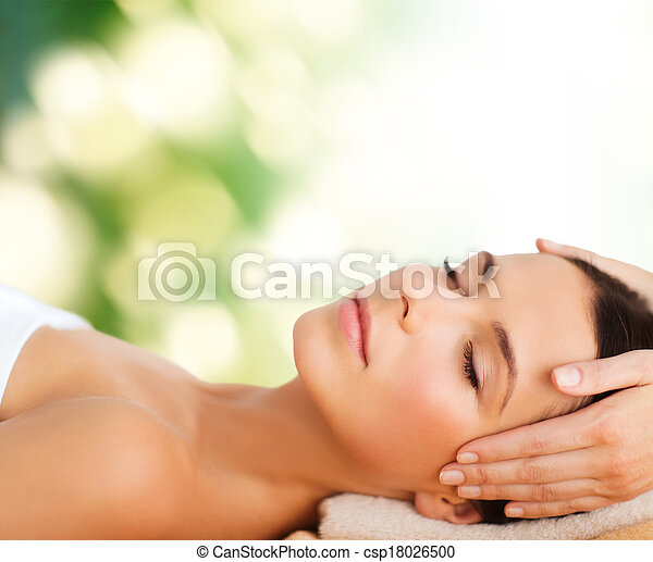 beautiful woman in spa salon having facial - csp18026500