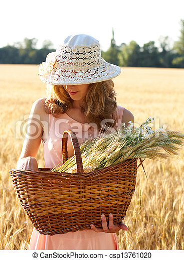 Beautiful woman in the hat with basket full of ripe ears - csp13761020