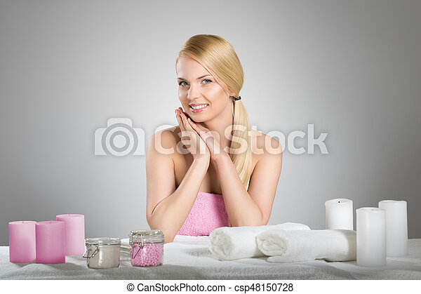 Portrait of beautiful woman in towel smiling behind table with spa accessories