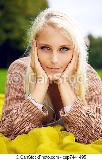 Beautiful woman lying in a park - csp7441495