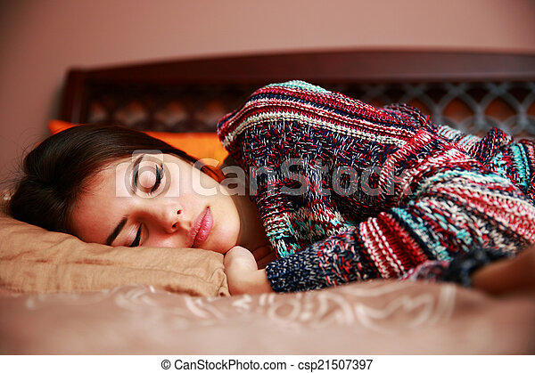 Beautiful woman lying on bed sleeping at home in the bedroom - csp21507397