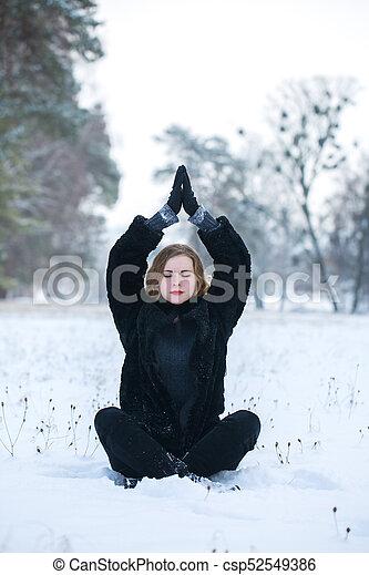 beautiful woman meditating in the park - csp52549386