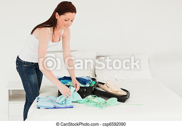 Beautiful woman packing her suitcase - csp6592090