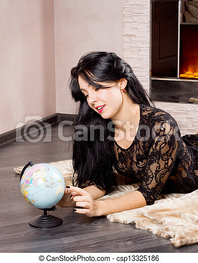 Beautiful woman playing with a globe - csp13325186