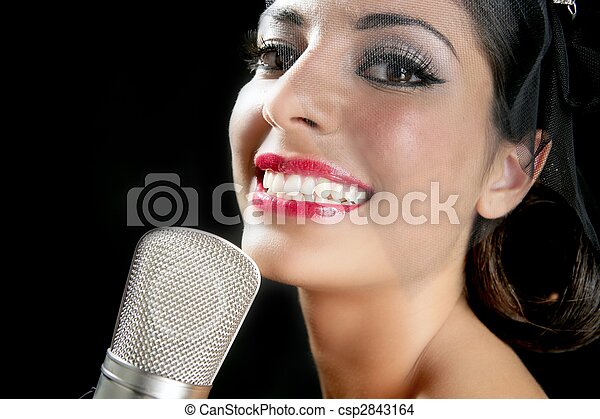 Beautiful woman singing on a vintage microphone - csp2843164