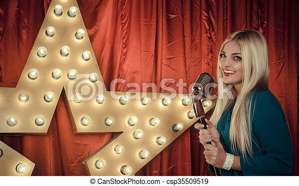 Beautiful woman singing on stage with microphone - csp35509519