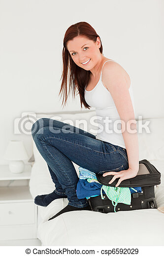 Beautiful woman sitting on her suitcase - csp6592029