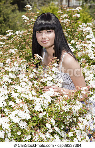 beautiful woman standing in a field with white flowers - csp39337884