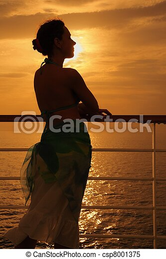 beautiful woman standing on deck of cruise ship and looking away. evening. - csp8001375