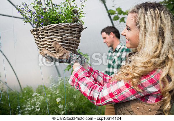 Beautiful woman touching a hanging flower basket - csp16614124