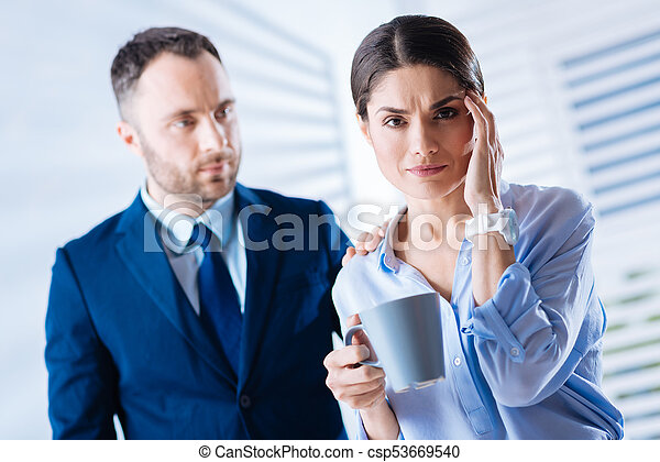 Beautiful woman touching her forehead while holding a cup of tea - csp53669540