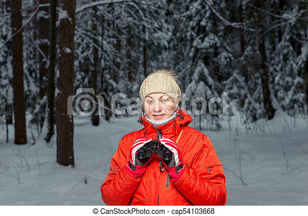 beautiful woman tourist with binoculars in a winter forest - csp54103668