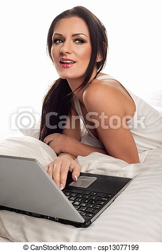 Beautiful woman using a laptop in bed - csp13077199