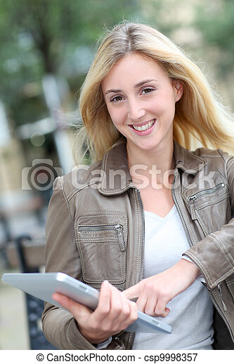 Beautiful woman using electronic tablet in public park - csp9998357