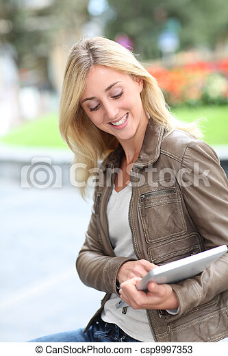 Beautiful woman using electronic tablet in public park - csp9997353
