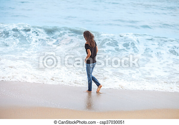 beautiful woman walking along sea in storm - csp37030051