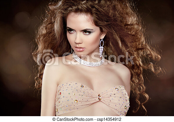 Beautiful woman with long brown curly hair and makeup. Hairstyle. Jewelry. Jewellery. - csp14354912