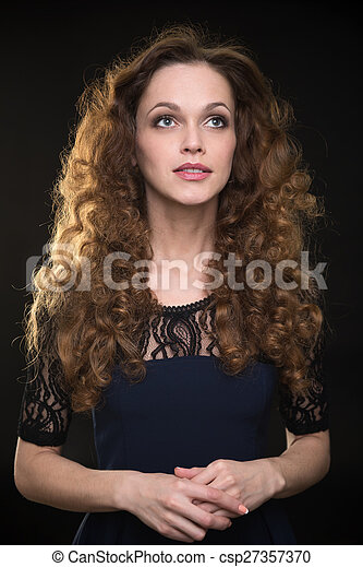 Beautiful woman with long brown curly hair - csp27357370