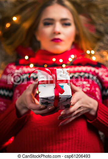 Beautiful woman with present box and festive lights - csp61206493