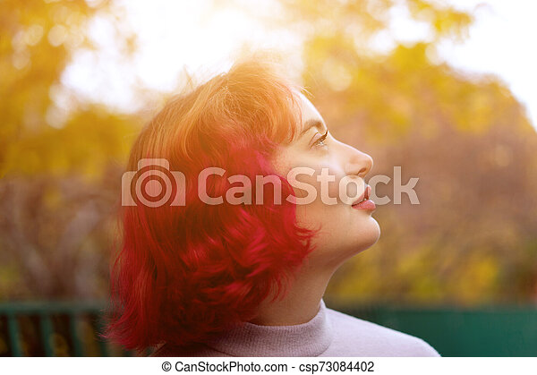 Beautiful woman with red dyed hair and background of autumn yellow leaves. - csp73084402