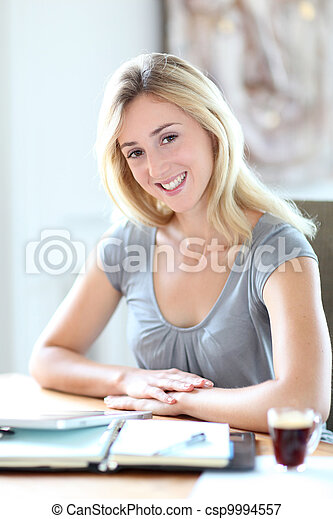 Beautiful woman working at home on agenda - csp9994557