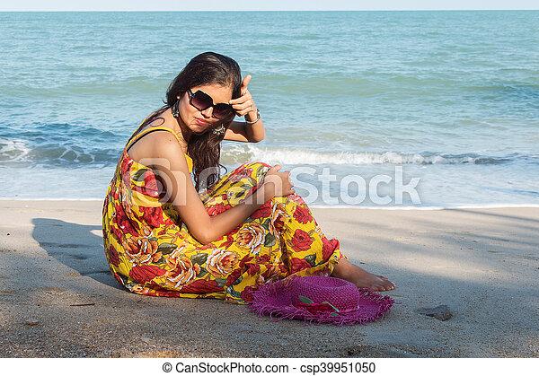 Beautiful women sitting on the beach - csp39951050